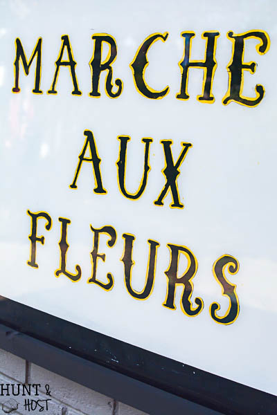 Get a vintage French feel with this DIY hand painted glass sign tutorial. The French flower market sign looks great on a patio or as large wall art. Marche Aux Fleurs!