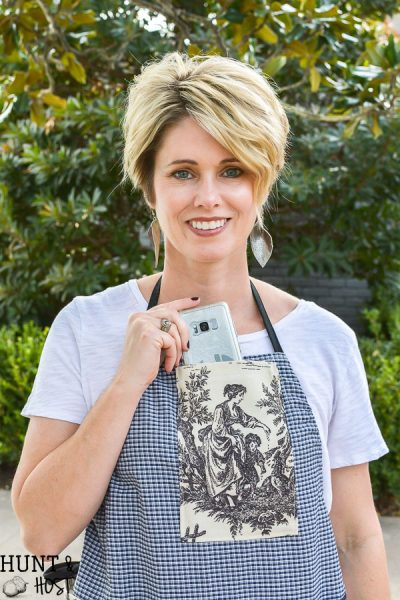 The perfect craft apron from fabric scraps, old clothes and linen closet toss outs. An easy pattern idea for how to make an apron from a shirt. This apron even has a cell phone pocket and hammer loop.