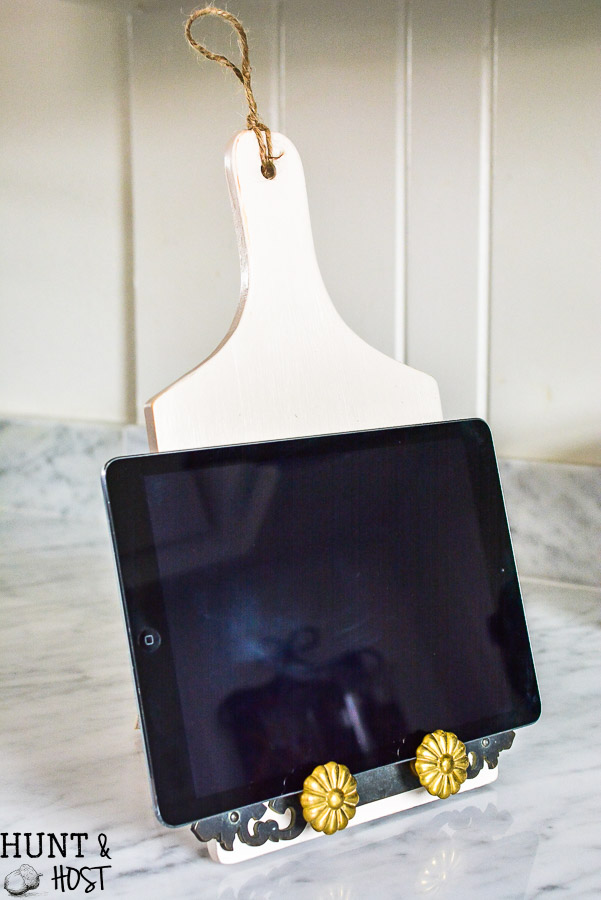 Dollar store decorating hacks for you to get your home decor on a dime! This dollar store DIY turns a wood cutting board into a tablet stand for recipe time in the kitchen.