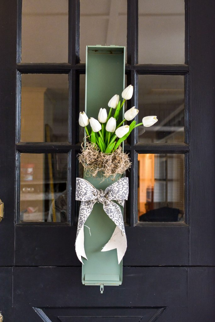 This white tulip wreath for the front door would look great as wall art too. Perfect for your spring decor this upcycled vintage safety deposit box was a unique Round Top Antiques Week find.