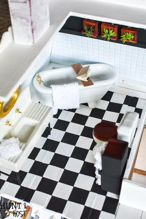 Dollhouse master bathroom decor ideas for a farmhouse bathroom. This tiny bathroom has it all, a claw tub, farmhouse sink, black and white checkered floor and cute DIY wall art.