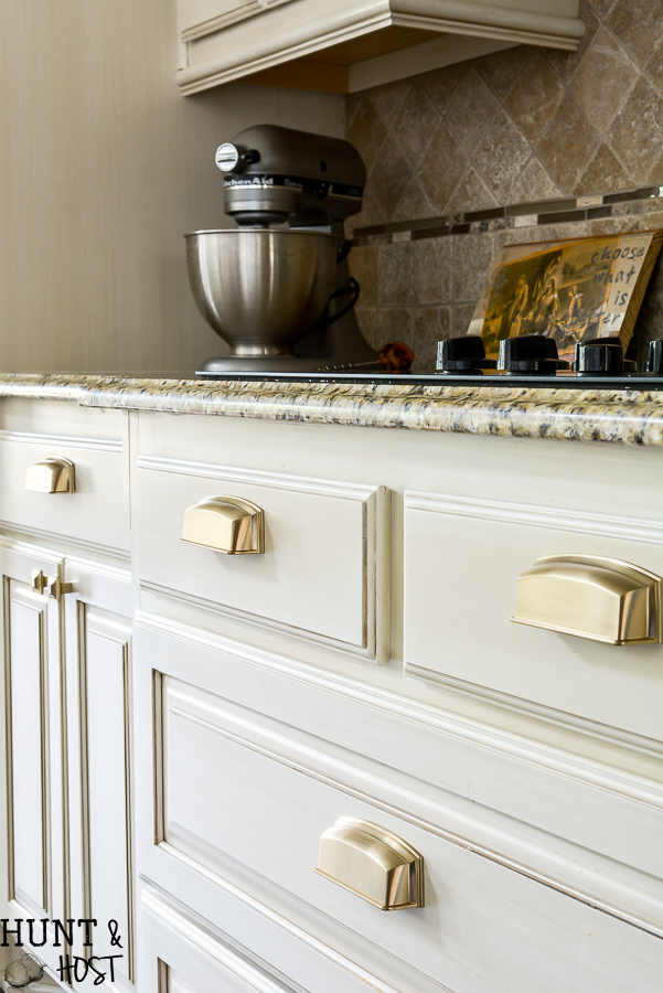 The kitchen got some jewelry with this glam French country hardware selection, plus some easy DIY hardware installation tips! #kitchenhardware #frenchcountrykitchen #goldhardware #kitchencabinetpulls #cuphandles #vintageglam