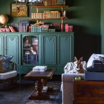 Try your hand at stylish storage with opening shelving and furniture made to look like a built in. This stunning moody green library room will answer the question , why open shelving over built-ins cabinets! #weekendproject #openshelving #goldaccents #libraryroomidea #studydecorideas #builtinbookcase #englishcountry