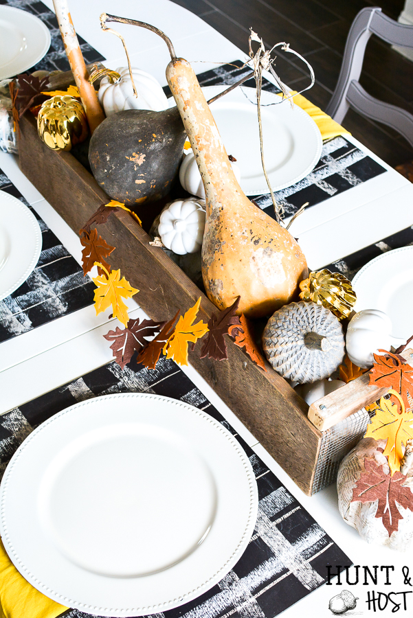 A simple fall table setting with buffalo plaid accents via chalkboard placemats. Layer on the metallic ad gold hues that are popular fall colors this year! CHeck out an entire array of simple fall décor inspiration from mantels to free printables, this post has it all! #chalkboard #meatllics #falltable #gourds #simplefall
