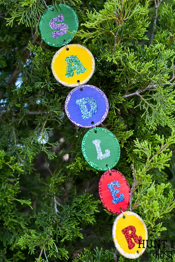 Make your own personalized Christmas ornament with your name, your kid's name or just fun Christmas sayings and words. This easy DIY takes no special tools or machines. You can make custom christmas ornaments to fit your color scheme and any name, even a christmas ornament for unusual names! Everyone loves to see their name in glitter and on the Christmas tree so make these special ornaments for the whole family. #handmadechristmas #christmastreeornaments #decoratethetree #nameinlights #DIYChristmasornament #glitterornament #easyDIYCHristmas