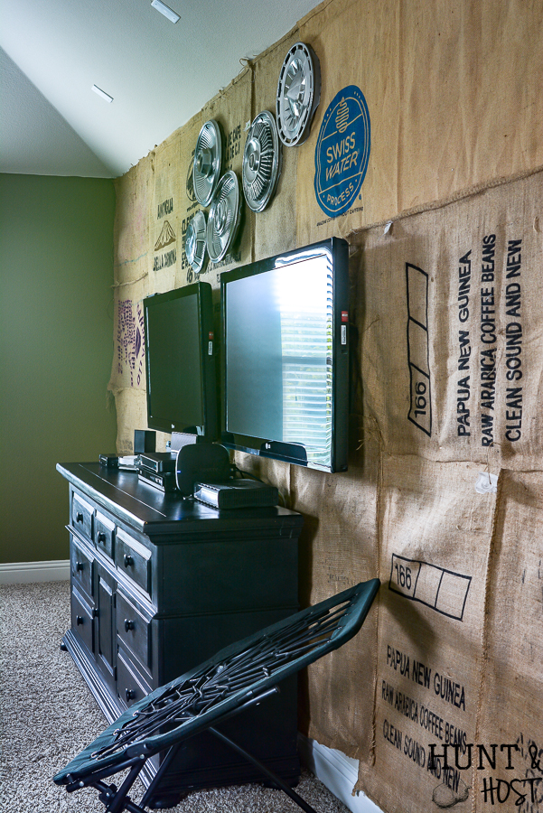 What a great game room idea! This rustic cabin lodge game room has great decorating ideas, a tutorial on how to hang a wall mounted TV (or two for a Fortnight lover's paradise!) plus an inexpensive DIY burlap wall covered in coffee bean sacks. All the elements for the perfect family game room with a cozy cabin style! #SANUS #SANUSspaces @SANUS @SANUSsystems #gameroomideas #burlapwalls #DIYwallpaper #mediaroom #TVmount #rusticroom #familyroomideas #rusticdecorideas